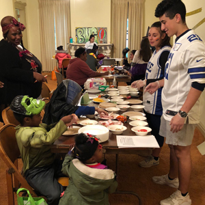 Emerging Leaders Program students serve snacks at a Halloween-themed Community Cafe for the North of Main Street community in Binghamton.