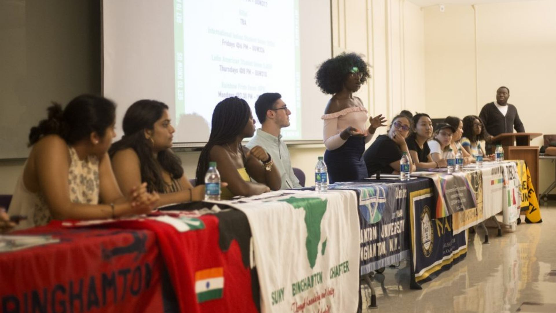 a panel of student organization leaders in front of a room with organization banners on the table and one female student leader at the podium speaking