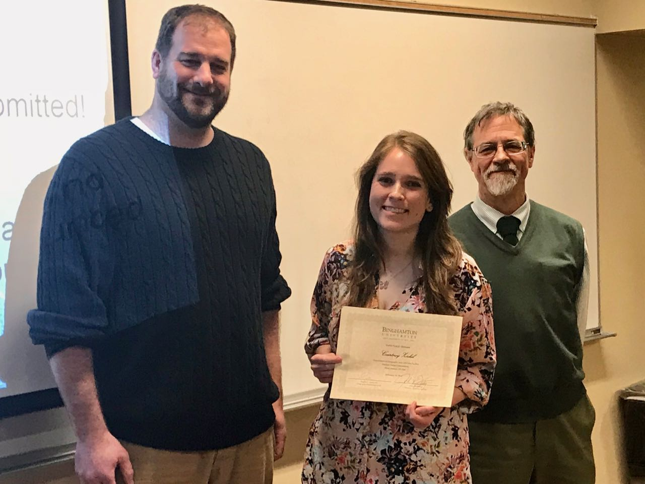 Kevin Heard and Lucius Willis presents Courtney Zirkel with an award at the third annual GIS Day, hosted by the geography department, on Friday.