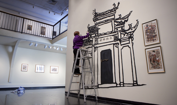 Jacqueline Hogan, assistant director of the University Art Museum, installs an exhibit for the celebration of the Chinese New Year that will showcase prints made on paper.