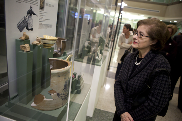 Louise Akel of Binghamton observes an exhibit of archaeological discoveries at the site of the University Downtown Center during a Jan. 6 reception marking the fifth anniversary of the College of Community and Public Affairs. Also on display was the Native-American hand-carved stone sculpture commemorating Haudenosaunee (Iroquois) heritage in the Confluence Park area, which was created by artists from the Onondaga Nation.
