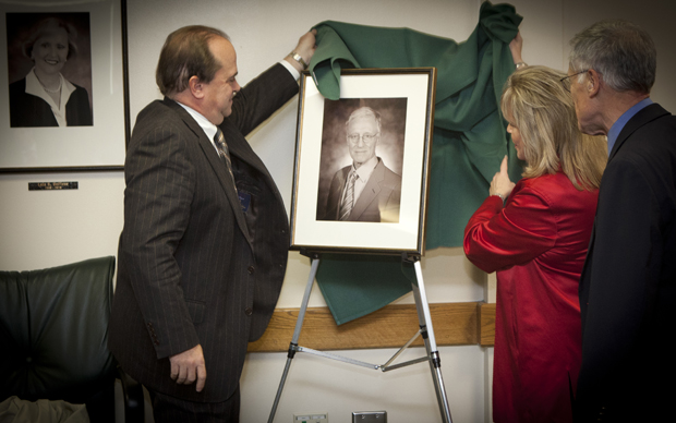 James Orband and Kathryn Grant Madigan unveil a photo of C. Peter Magrath at the conclusion of the council's meeting Dec. 16.