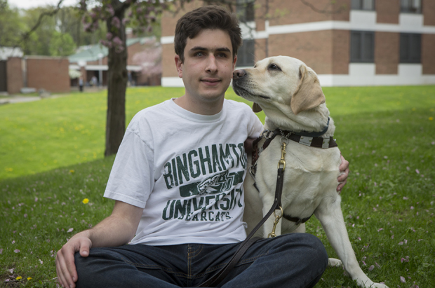 Michael Forzano sits with his Labrador guide dog, Delta. Forzano suffers from a genetic disorder that took away his sight and limits his hearing.