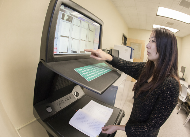 Shengsheng Zhou, past president of the Graduate Student Organization, tests a new book scanner at a new study space dedicated to graduate students at the Glenn G. Bartle Library.