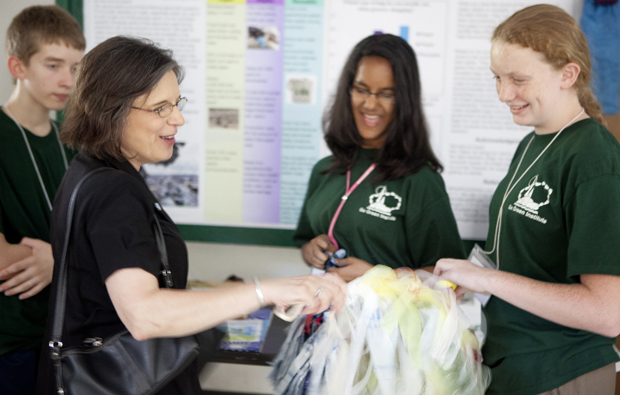 New York State Assemblywoman Donna A. Lupardo shakes a pom-pom made of recycled plastic grocery bags as she visits the poster session  of the Go-Green Institute, which features local middle-school students who excel in math and science, at the Lecture Hall on July 22. Campers Christopher King, 13, left, of West Middle School in Binghamton; Maitri Mangal, 12, center, of Union-Endicott Middle School; McGinnis Miller, 12, of Maine-Endwell Middle School; and Yvonne Raychawdhuri, 13 of Vestal Middle School (not pictured), experimented on which plastic bags were best for the environment.