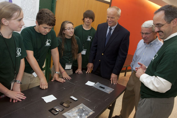 From left to right, Maia Wright, 12, and Alexander Decker, Acacia Madison and Brandon Vosbury, all 13, present their poster about how to dispose of cell phones to President Harvey Stenger, Time Warner Cable's David Whalen and Go Green Director Wayne Jones.