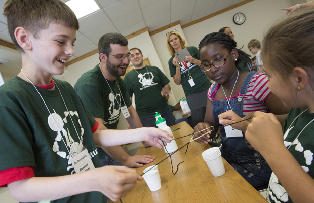 Binghamton University, in partnership with the Binghamton City School District, hosts its 6th annual Go Green Institute summer science program, designed to excite students about science, math and engineering. Through Go Green, students explore issues of science, math and engineering as they relate to creating a sustainable living environment. Pictured here, sixth graders Alexander MacBlane, Leila El-Begearmi and Alexandra Tucker use sting and rubber bands to stack plastic cups during a teamwork exercise as chemistry PhD student Steve Boyer looks on.
