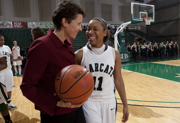 Andrea Holmes receives a game ball from Head Coach Nicole Scholl before a game at the Events Center on Jan. 29. Holmes was honored for passing the 1,000-point career scoring mark as a Bearcat during a game at the University at Albany last week.