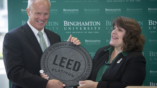 President Harvey Stenger and Tracie Hall, executive director of the state chapter of the U.S. Green Building Council, share a laugh about how heavy the LEED©  Platinum plaque is before seeing it mounted on a wall of the Engineering and Science Building.