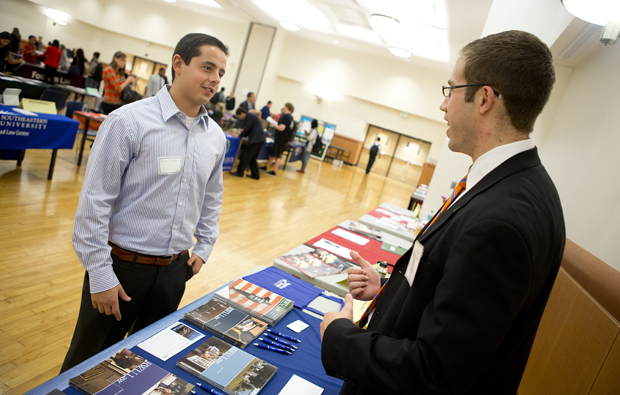 David Watters, a philosophy, politics, and law major from Cleveland, left, speaks with alumnus Peter M. Eraca '05, who is now an admissions councilor with Roger Williams University School of Law in Rhode Island, during Law Day at the Mandela Room on Oct. 3.