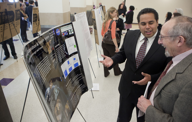 Distinguished Professor of History Thomas Dublin speaks with Robert Dextre, a senior mechanical engineering major from New York City, about his research on cryogenic acquisition and transfer systems at a Binghamton Research Days event on April 25. Dextre, who plans to pursue a doctorate in aerospace engineering at the University of Alabama at Huntsville, was an intern at NASA last summer.