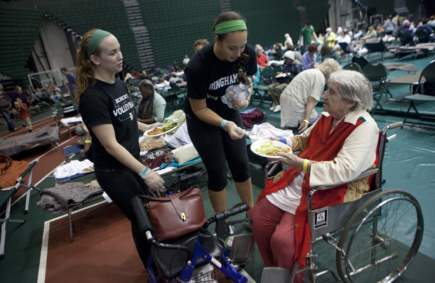 Binghamton University student-athletes Jordyn Suhr, left and Grace Vickers, both members of the volleyball team, serve food to Marian Price of Binghamton at a Red Cross shelter at the Events Center on Sept. 8.