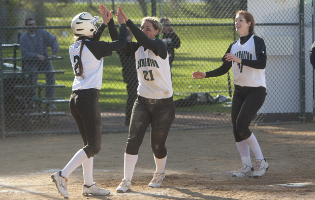 Mikala King, center, and Chelsea Horne, right, greet Colleen Dougherty at home plate after Dougherty scored the go-ahead run on a Jessica Bump single in the seventh inning against Siena on March 27.