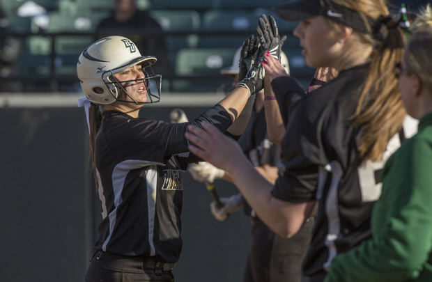 Third baseman Crysti Eichner is congratulated by her teammates after scoring a run against St. Bonaventure on April 1. The Bearcats took two games from the Bonnies.