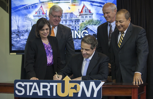 Gov. Andrew Cuomo, flanked by (left to right) Assemblywoman Donna Lupardo, Sen. Thomas O'Mara, Binghamton University President Harvey Stenger and Sen. Thomas Libous, signs the recently passed Start-Up NY law.