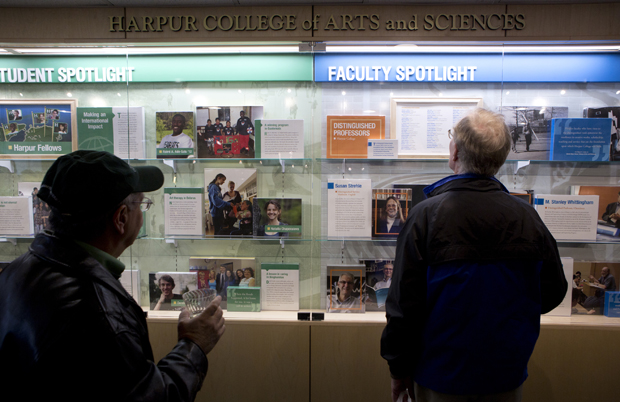 Guests at the Harpur College Quad and Wall of Excellence dedication look at the wall during the ceremony on Oct. 13. The Wall of Excellence, located near Jazzman's Cafe at the entrance of the Library Tower, highlights Harpur's history, students, faculty and alumni.