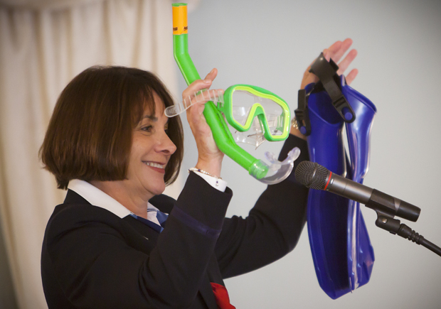 Flight attendant Sheila Dail holds up some swimming gear at the start of her Oct. 28 talk to the Binghamton University Forum at Traditions at the Glen in Johnson City.