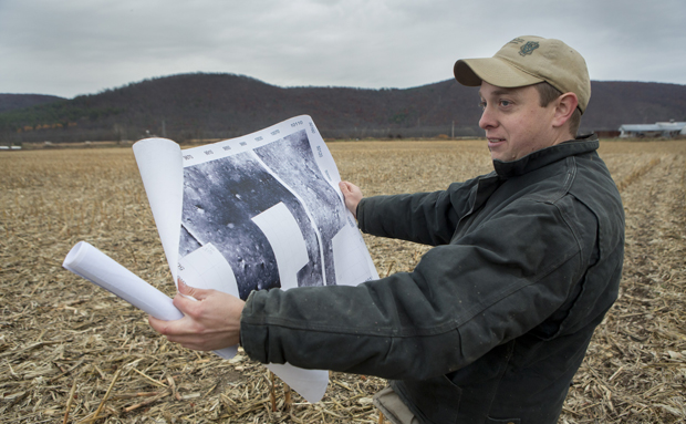 Michael Jacobson, battlefield research coordinator for the Public Archaeology Facility of Binghamton University, examines a printout that indicates where artifacts may be located at the Chemung battlefield.