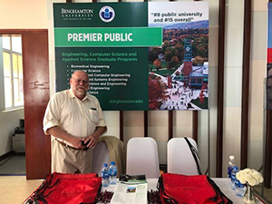 Professor Roy McGrann in Vietnam in front of a Binghamton University poster promoting our programs.
