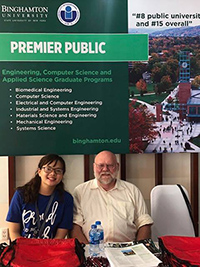 Professor Roy McGrann with a student in Vietnam in front of a Binghamton University poster promoting our programs.