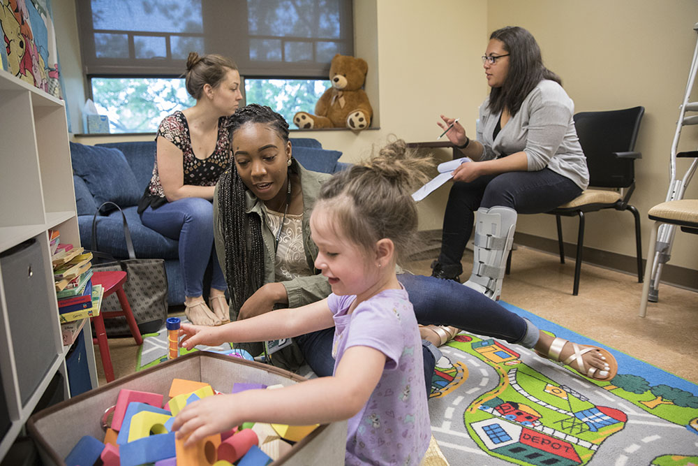 Taylor Hitchcock (right) in summer 2017 working as part of Bridges to the Baccalaureate program with transfer student Jazlynn Gray with children and their mothers in Peter Gerhardstein's lab.