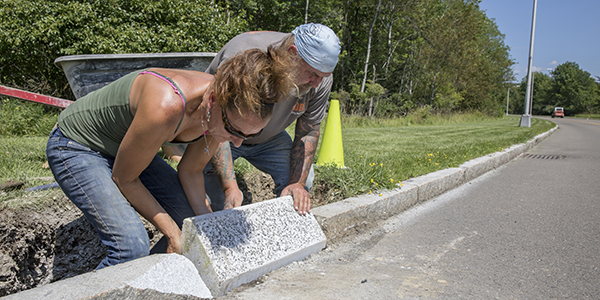 Michelle Rich and Doug Fergerson of Physical Facilities install one of thirty-eight 300-pound concrete ramps into the curbing of the Connector Road in July 2017. The ramps aid in the migration of yellow-spotted salamanders that travel from one side of the road to the other.