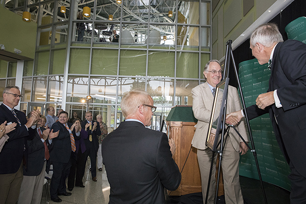 Distinguished Professor of Chemistry and Materials Science M. Stanley Whittingham, second from right, shakes Provost Donald Nieman's hand as President Harvey Stenger and the crowd at the opening of the Smart Energy Building applaud.