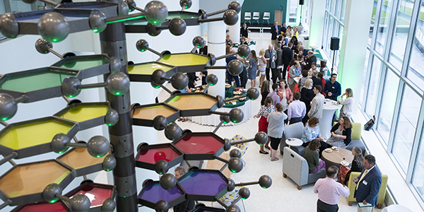 People gather in the atrium of the School of Pharmacy and Pharmaceutical Sciences following tours of the building given during a VIP reception Aug. 13.