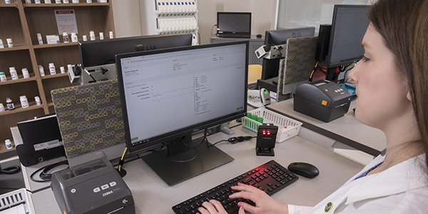 Sarah Lynch, assistant clinical professor of pharmacy practice, uses a software system she is developing with colleagues that will improve the student educational experience for dispensing prescriptions.