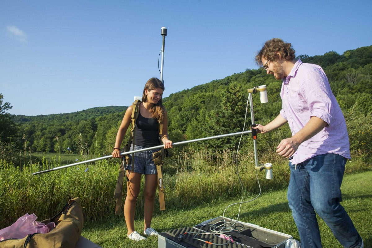 Natalia Romanzo, a master's student in sustainable communities, wears a Geometrics G-858 cesium vapor magnetometer and battery pack on August 8, 2019. The sensing equipment, which weighs about 40 pounds, is still being used, but drones are increasingly providing a more practical alternative for remote sensing. Timothy de Smet, Environmental Visualization, Research Assistant Professor with the First-Year Research Immersion Program, helps Natalia with the pack.