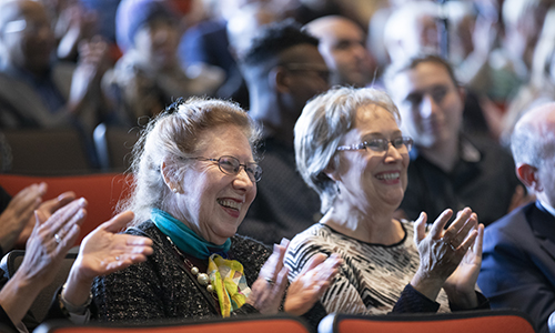 Whittingham's wife, Georgina Whittingham, left, a professor of Spanish and Latin American literature at the State University of New York at Oswego, and Elaine Schmitz, Whittingham's longtime administrative assistant, applaud as he walks onto stage.