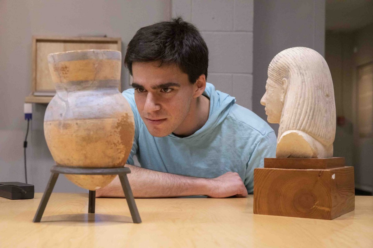 Binghamton University senior Doug Braun studies a vase and a bust from ancient Egypt for his curation project,