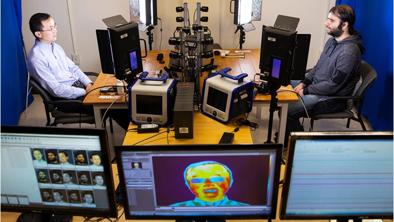 """Umur Ciftci, a PhD student in computer science, poses for a 3D scan in Professor Lijun Yin's lab at the Innovative Technologies Complex. Ciftci's doctoral thesis will focus on detecting """"deepfake"""" videos."""