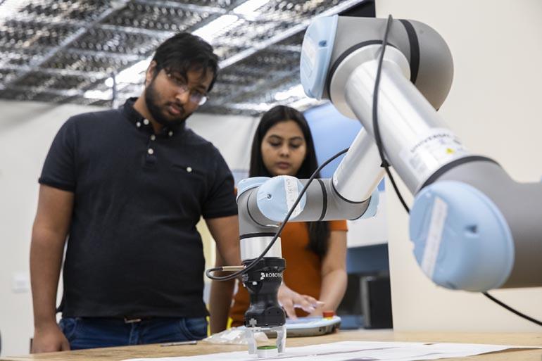 Working in the Autonomous Intelligent Robotics Lab are PhD students Kishan Chandan, left, and Vidisha Kudalkar.