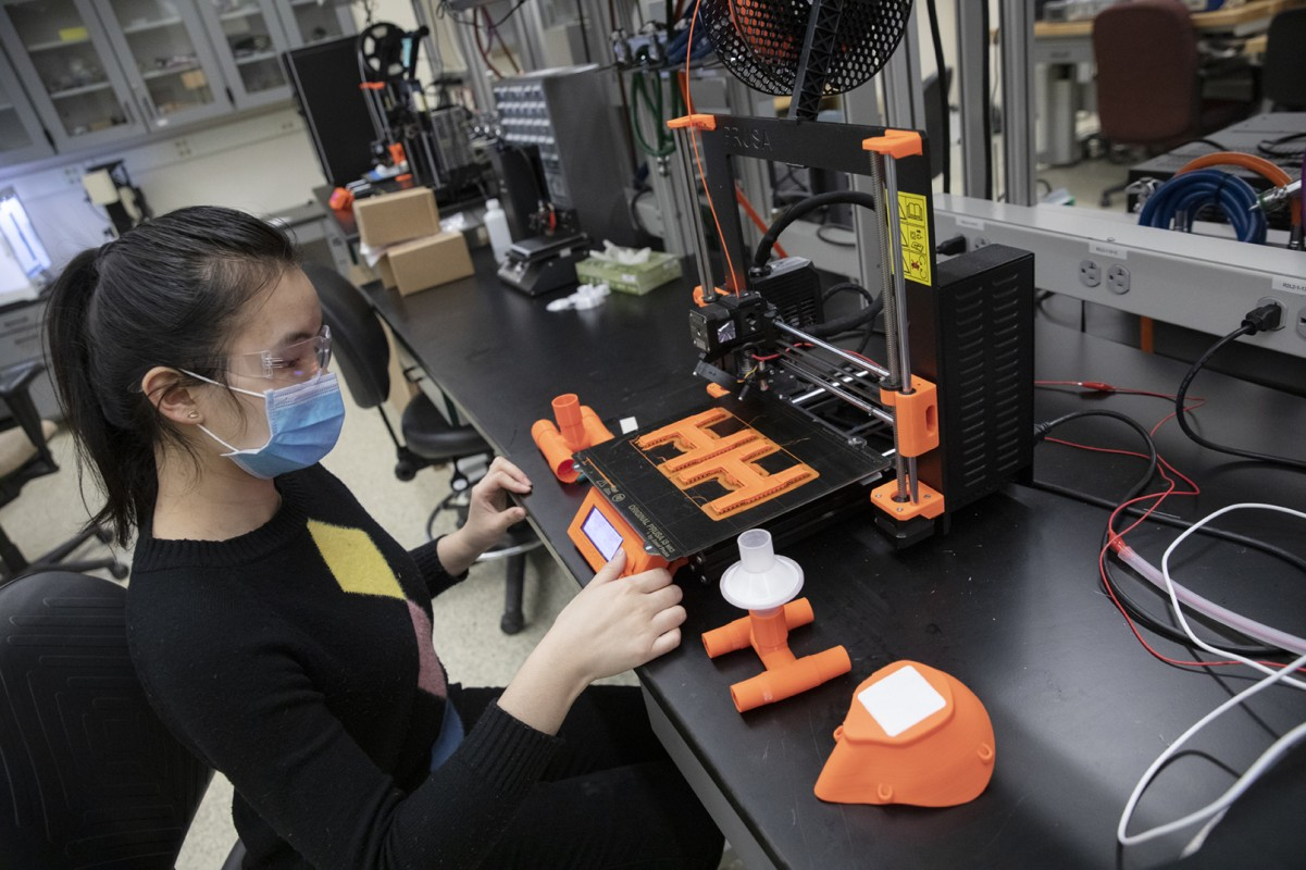 Huimin Zhou, a PhD student in Department of Systems Science and Industrial Engineering, oversees the 3D-printing of ventilator adapters and facemasks at a lab in the Innovative Technologies Complex. The equipment will be donated to local hospitals to aid the fight against the COVID-19 pandemic.