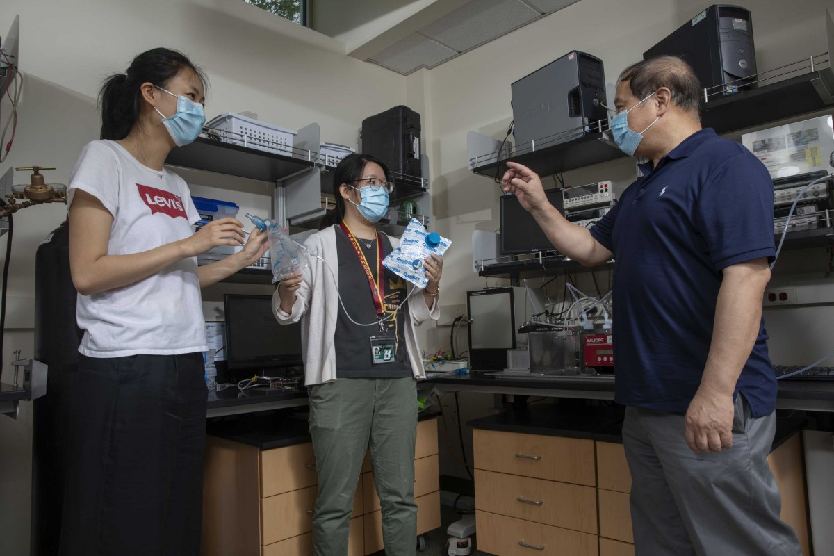 Graduate students Stacey Shan Wang and Sally Guojun Shang with Chuan-Jian Zhong, professor of chemistry, photographed at Zhong's laboratory in the Smart Energy Building at the Innovative Technologies Complex.
