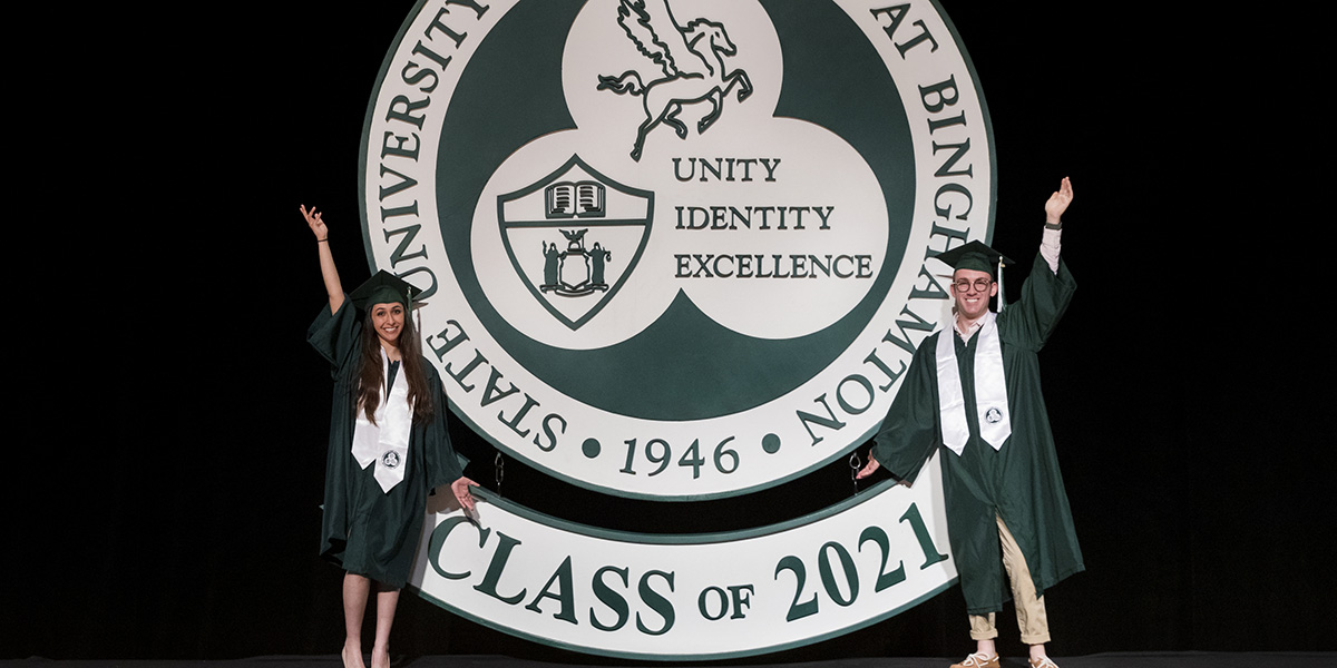 Maya Kallman '21, intern in the Office of the President, who will receive double degrees in business administration and graphic design, and Zachary Herz '21, student representative to the Binghamton University Council, who will receive a degree in psychology, pose with the large University seal following the taping of the 2021 Virtual Commencement Ceremony.