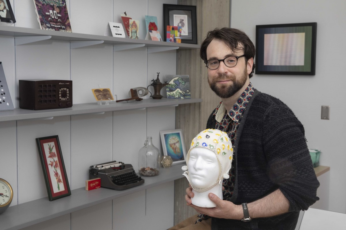 Assistant Professor of Psychology Nicholas Gaspelin holds an electroencephalography cap.