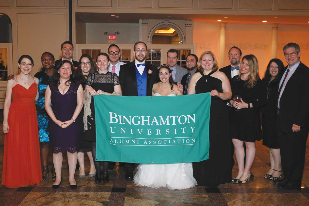 Knowing there would be quite a few Binghamton alumni at the wedding, Brian asked the Alumni Association for a school banner to use in some of the photos. Pictured here, from left: Sara (Miller) Fox '09, Lois Young '06, Diane Napolitano '06, Mike Schordine '05, Katherine McCrink '06, Amber Beckley Largeaud '06, Jared Gilman '08, Brian Miller '05, Meryl (Mandelbaum) Miller '10, Jason Wand '06, Joe Frankino '05, Lindsey (Krecko) Yates '04, Rich Ziolkowski '04, Nicole (Papadopoulos) Ziolkowski '04, Jennifer Katz '05 and Josh Shapiro '03. Also in attendance, but not pictured: Marissa (Forman) Wright '05, and Jeremy Wright and Beth (Kaufman) Solomon, both '06.