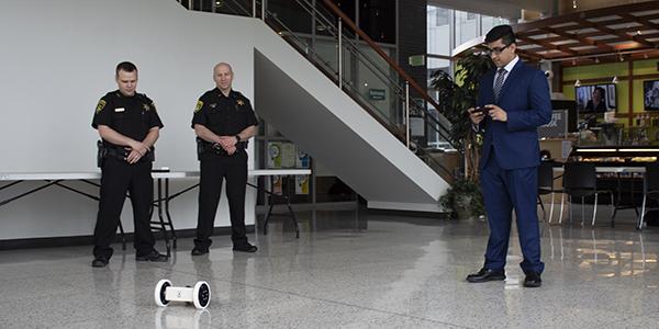Avishek Paul, a member of the Reconnaissance Robot senior design team, demonstrates the robot's capabilities for members of the Tioga County Sheriff's Department.
