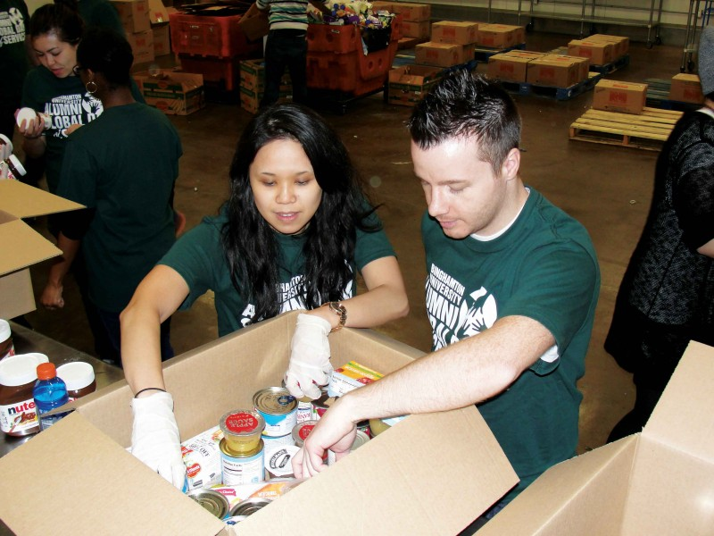 Carol Luong '08, MBA '09, and co-founder Matthew Martindale volunteer at a food pantry during the Alumni Global Day of Service in 2015.
