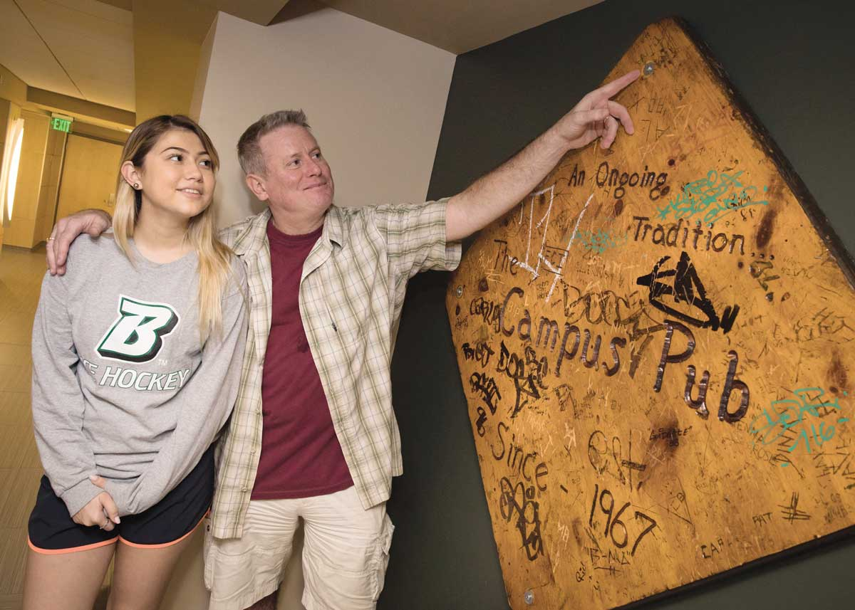 "On a recent visit to the Alumni Center, Ray Scanlon '85 and Tina Chan '84 found a table from the old Campus Pub on display. ""The table has our initials carved in it — done while we were dating,"" Scanlon says. The couple has been married for 24 years; their daughter Kaitlyn will be a sophomore in the fall."