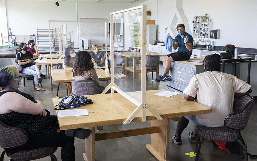 Colin Lyons, an assistant professor in the Department of Art and Design, teaches a Printmaking class in the Fine Arts Building as students sit 6 feet apart with masks on.