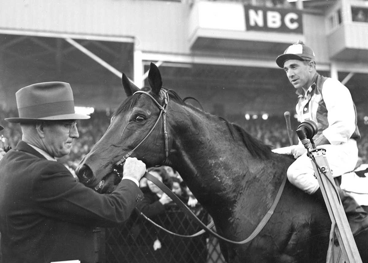 Seabiscuit with jockey George Woolf and trainer Tom Smith after beating War Admiral in 1938 at Pimlico.