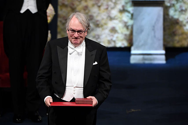 Binghamton University Distinguished Professor M. Stanley Whittingham bows to the audience after receiving the Nobel Prize in Chemistry from King Gustaf of Sweden at the Stockholm Concert Hall Dec. 10.