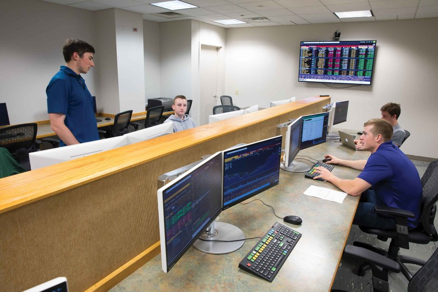 Students in the Zurack Trading Room discuss various companies and their potential for stock trades as they make decisions for the Binghamton University Zurack Trading Room and Investment Fund.