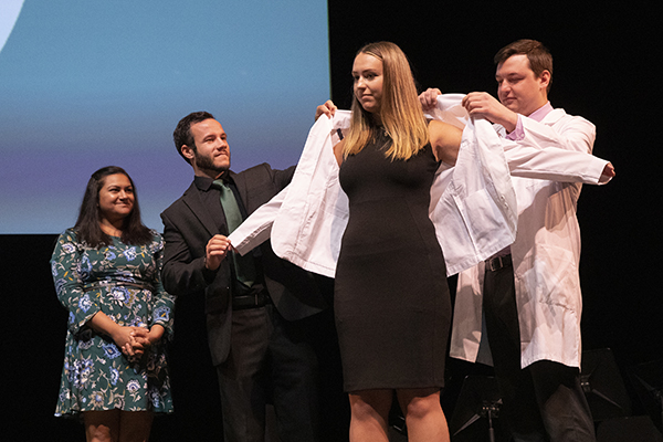 Hannah Surdi, is coated by her brother, Tyler Surdi, right, with assistance from Binghamton University Assistant Professor of Pharmacy Practice H Andrew Wilsey. Sara Spencer, clinical instructor and IPPE coordinator of pharmacy practice, looks on.