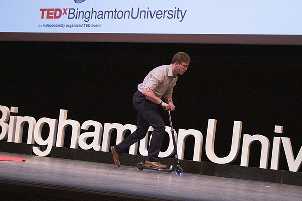 Binghamton University junior Jonathan Caputo rides onto the TEDxBinghamtonUniversity stage on a scooter before giving his