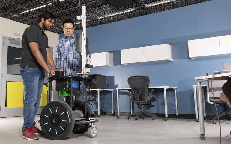 Assistant Professor Shiqi Zhang, right, runs the Computer Science Department's Autonomous Intelligent Robotics Lab at the Watson School. Pictured with Zhang is PhD student Kishan Chandan.