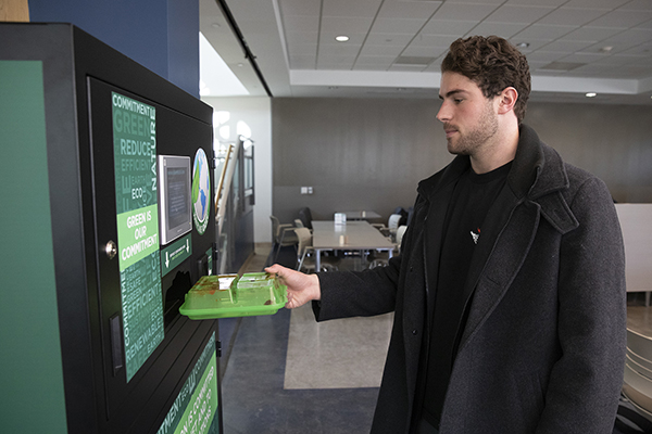 Sophomore Michael Kucza uses the new OZZI system that allows patrons of Binghamton University dining halls to use reusable food containers that can be returned to a vending machine after use.